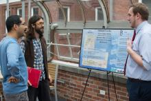 Student discussing poster with faculty member and another student