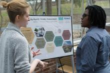 Student talks to faculty member about poster